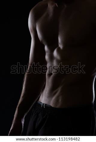 Closeup on muscular male torso with abdominal muscles on black - stock photo