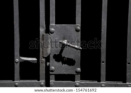 Closeup on old rusty metal bar door with old-fashioned lock - stock photo