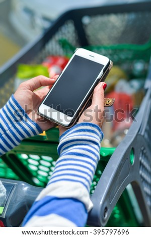 Closeup on person holding mobile phone in hand during shopping. Cart on store background shopping - stock photo