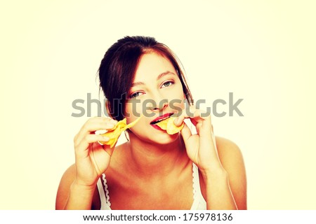 Closeup on pretty teen caucasian girl eating chips.