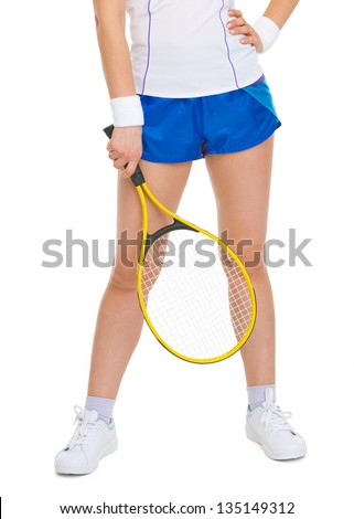 Closeup on racket in hand of tennis player near legs - stock photo