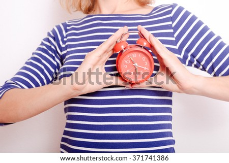 Closeup on red alarm clock in female hands on white background - stock photo