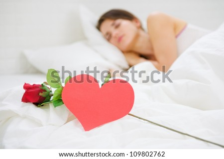 Closeup on red rose and heart shaped postcard near sleeping woman