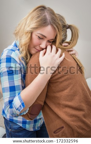Closeup on sad teen daughter crying by problems in the shoulder of her mother. Mother embracing and consoling daughter. - stock photo