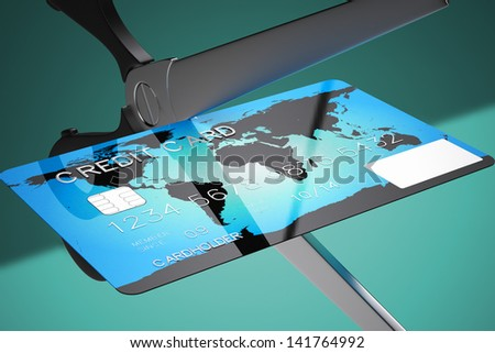 Closeup on scissors cutting credit card on a green background. Might represent recession, bankruptcy or any financial related matters. - stock photo