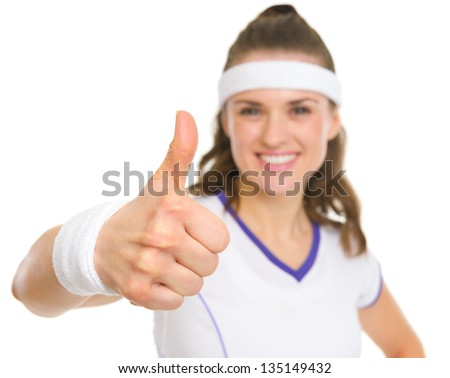 Closeup on smiling female tennis player showing thumbs up
