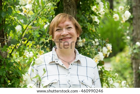closeup on smiling senior woman outdoors on sunny summer day