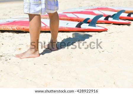 Closeup on surfer legs with surfing board ocean beach background outdoors - stock photo