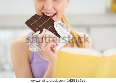 Closeup on teenage girl reading book and eating chocolate - stock photo