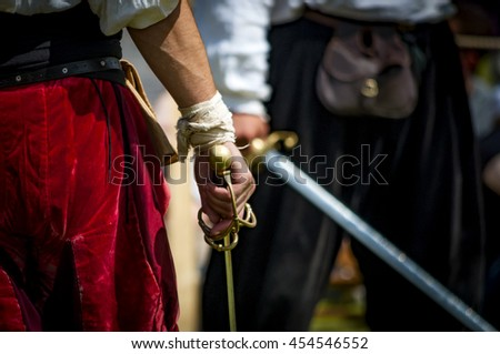 Closeup on the hand holding a sword of a pirate or medieval warrior, preparing to duel another man, there is a bandage on his wrist and the man in the background is blurry - stock photo