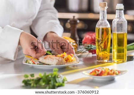 closeup on the hands of a chef in a professional kitchen carefully depositing a sprig of dill on a cod fillet