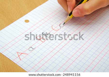 Closeup on the hands of a child doing writing activity as part of homework. School concept - stock photo
