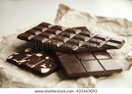 Closeup on three different rustic chocolate bars freshly baked with oats, nuts and cacao beans, on craft paper, isolated on white table - stock photo