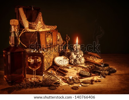 Closeup on treasure still life, luxury vintage accessories, pirates booty, bottle with rum, fish skeleton, cigars and golden coins, dangerous adventure concept - stock photo