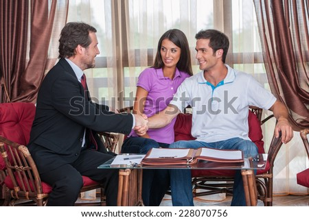 closeup on two man handshaking to signed agreement. agent looking at young couple purchasing new house and shaking hands - stock photo