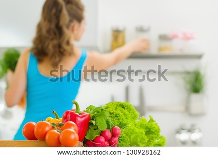 Closeup on vegetable and young housewife in background