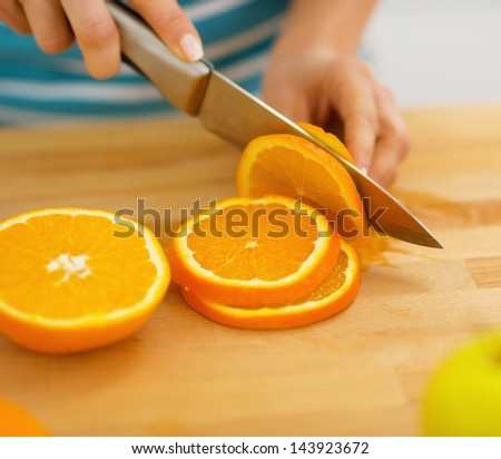 Closeup on woman cutting orange - stock photo