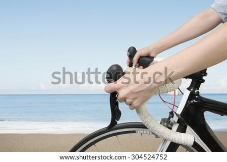 Closeup on woman hands riding a bike, with blue sky sea beach background. - stock photo
