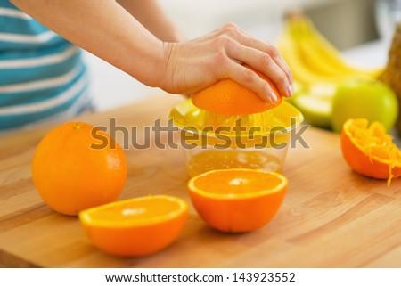 Closeup on woman making orange juice - stock photo