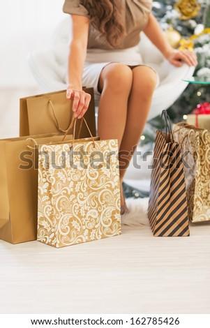 Closeup on woman sitting among shopping bags near christmas tree - stock photo