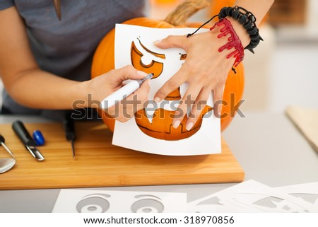 Closeup on woman using stencils to carve big orange pumpkin Jack-O-Lantern for Halloween party. Traditional autumn holiday - stock photo