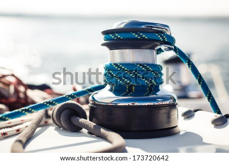 Closeup on yacht cord crank, rope holder on white sail background - stock photo