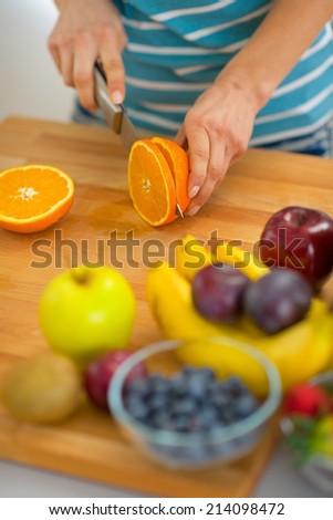 Closeup on young woman cutting orange - stock photo