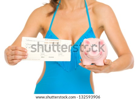 Closeup on young woman in swimsuit showing air tickets and piggy bank - stock photo
