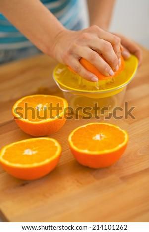 Closeup on young woman making fresh orange juice - stock photo