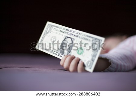 closeup one dollar banknote in hand of blonde caucasian baby nineteen month age with pink and white stripped jersey sleeping on brown sheets king bed - stock photo