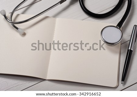 Closeup open notebook with blank pages with stethoscope, pen and glasses on a white doctor's table. Free space for text. Copy space. Top view - stock photo