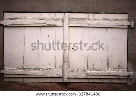 Closeup outdoor locked retro old timber wooden painted white peeling window shutters against grey concrete facade wall background for privacy and defence, horizontal picture - stock photo