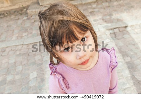 Closeup outdoor portrait of funny cute Caucasian blond baby girl in pink - stock photo
