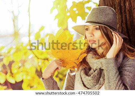 Closeup outdoors portrait of gorgeous young blonde Caucasian woman wearing gray autumn outfit, outdoors in park on sunny fall day. Beautiful girl in gray floppy hat and shawl. Retouched, vibrant color