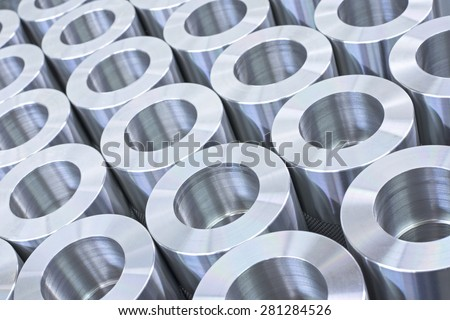 Closeup pattern of shiny circular precision stainless steel industrial machine parts arranged in rows - stock photo