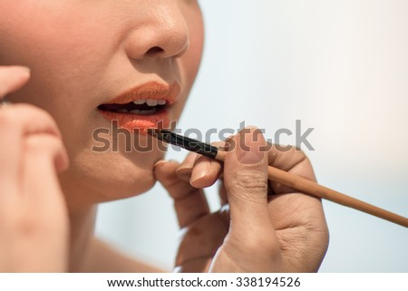 Closeup photo, brush painting on lips by makeup artist