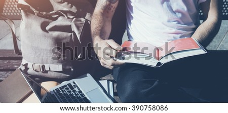 Closeup photo man wearing white tshirt sitting city park bench and reading book. Studying at the University, working new project. Books, laptop, backpack bench. Horizontal mockup - stock photo