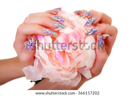 Closeup photo of a beautiful female hands with multicolored manicure and flower of peony on white background - stock photo