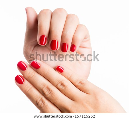 Closeup photo of a beautiful female hands with red nails isolated on white background