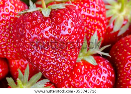 Closeup photo of a big heart shaped strawberry with stems on it - stock photo