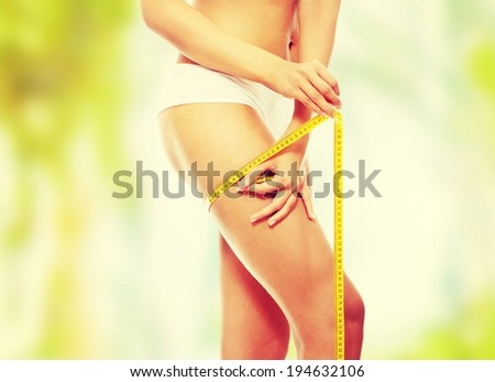 Closeup photo of a Caucasian woman's leg. She is measuring her thigh with a yellow metric tape measure after a diet
