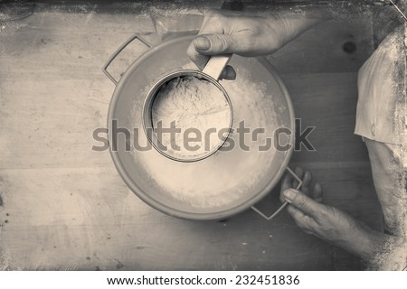 Closeup photo of a chef lady sifting flour for kneading. Black and white, directly above - stock photo