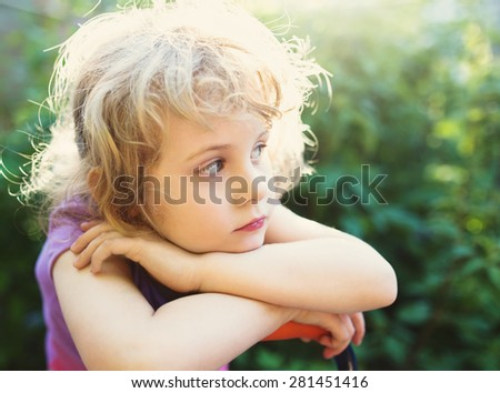 Closeup photo of a dreaming beautiful little girl outdoor - stock photo