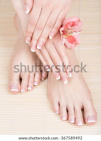 Closeup photo of a female feet at spa salon on pedicure and manicure procedure - Soft focus image - stock photo