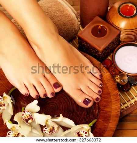 Closeup photo of a female feet at spa salon on pedicure procedure. Legs care concept - stock photo