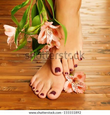 Closeup photo of a female feet at spa salon on pedicure procedure - Soft focus image - stock photo
