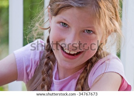 Closeup photo of a pretty 8 year old Caucasian girl smiling and happy.  She's got long brown hair and braided in pig tails. - stock photo