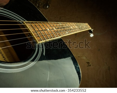 Closeup photo of an acoustic guitar played by a man. Only hands visible. Unrecognizible guitar player.