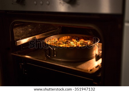 Closeup photo of apple pie baking in oven at kitchen - stock photo