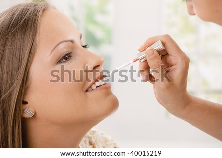 Closeup photo of applying makep on beautiful young woman.